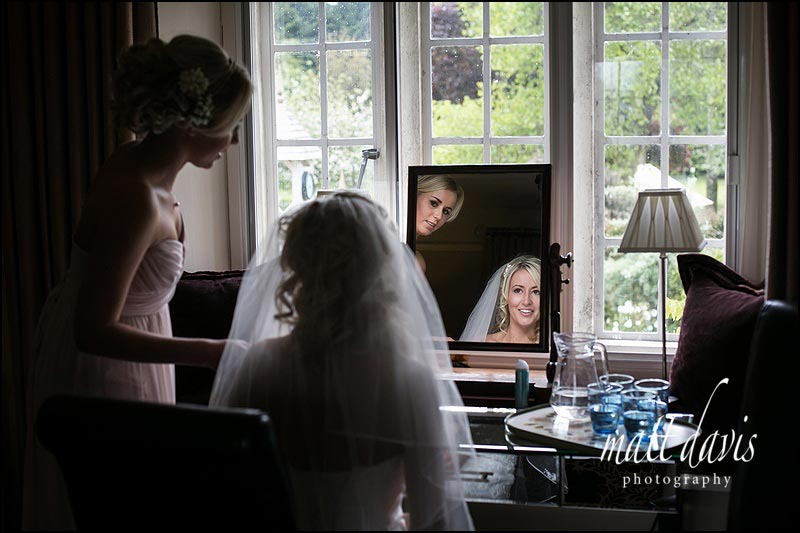Bride with veil looks in mirror and smiles at bridesmaid