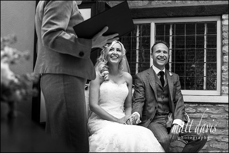 Couple sit whilst registrar reads vows during a wedding at Friars Court