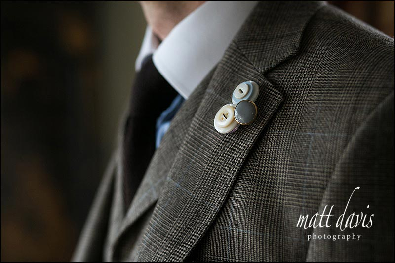 Unusual wedding broach with buttons as the grooms button hole
