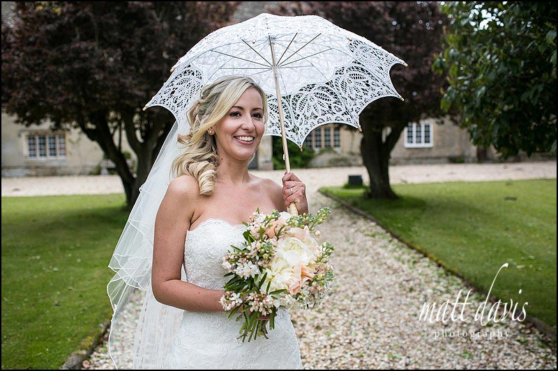 Bride with lace umbrella having photos at Friars Court on her wedding day