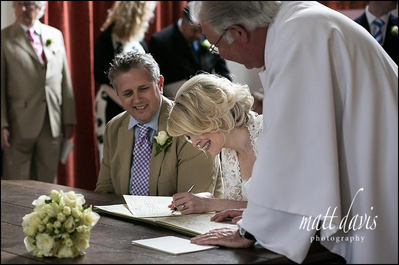 Bride and groom signing wedding register at Horsley Church, Gloucestershire