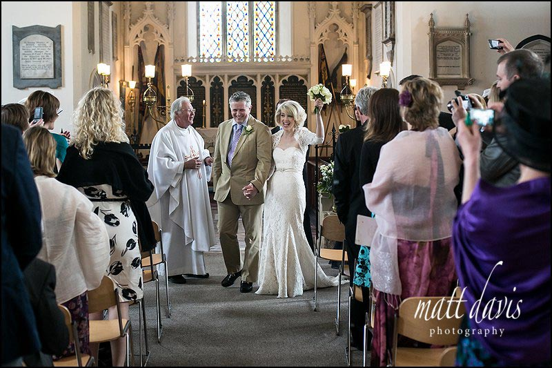 Wedding photo of couple walking down the aisle at St Martin's Church Horsley Gloucestershire