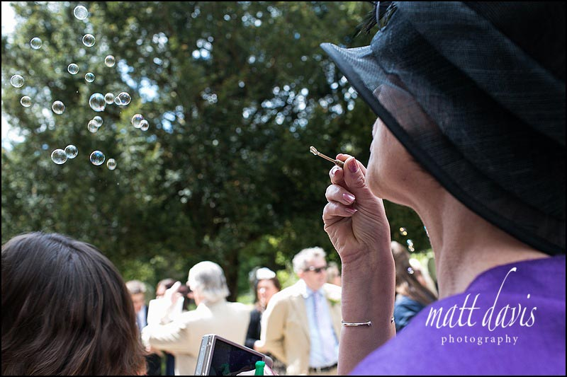 Wedding guests blowing bubbles at a wedding in Gloucestershire