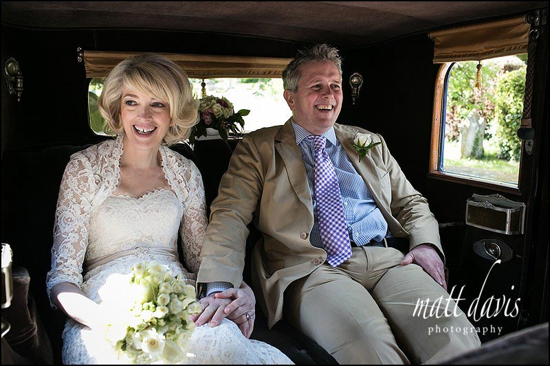 Married couple in vintage wedding car about to leave for wedding reception at the Hare and Hounds, Tetbury