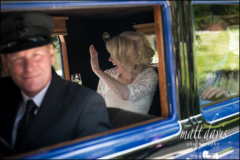 Bride waving as she leaves church to go to the Hare and Hounds wedding reception