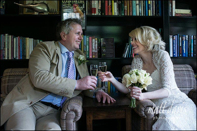Wedding couple enjoying a drink at their wedding reception at the Hare and Hounds, Gloucestershire