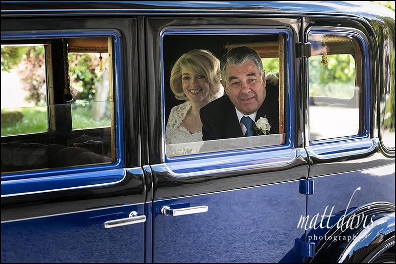 Bride and her father arriving in vintage wedding car for the wedding at Horsley Church, near Stroud