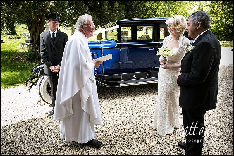 Bride and her father greeted by the vicar outside Horsley Church near Nailsworth