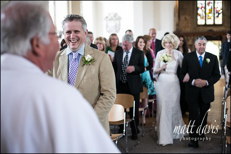 Wedding photo of groom as bride walks down the aisle at St Martin's church, near Nailsworth
