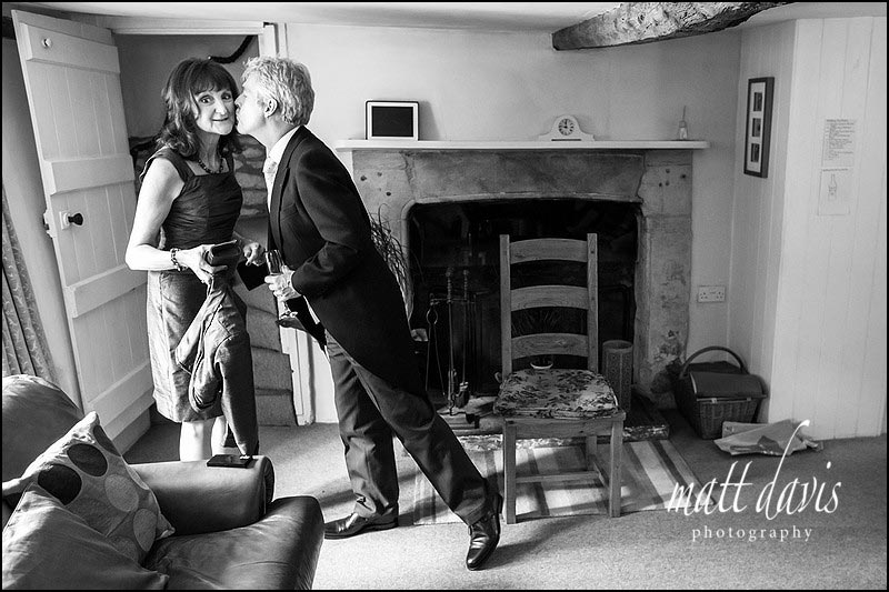 black and white wedding photo of mother and father of bride kissing
