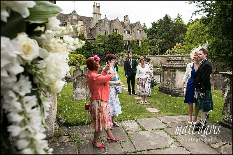 Wedding guests outside St. Mary's church, Bibury, Gloucestershire