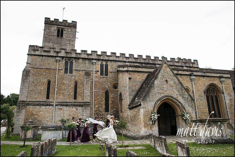 Brides veil blows off as she gets to St Mary's Church, Bibury, Gloucestershire