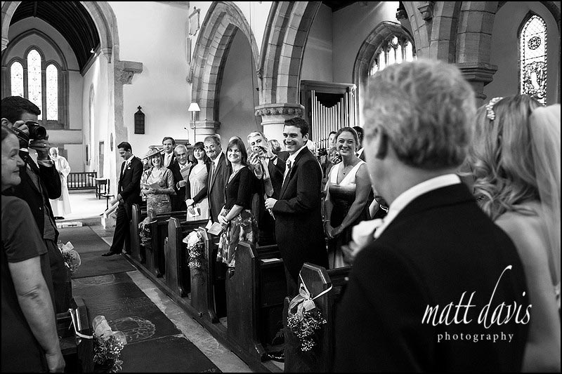 Documentary wedding photographer takes photo of guests expressions as bride walks down aisle.