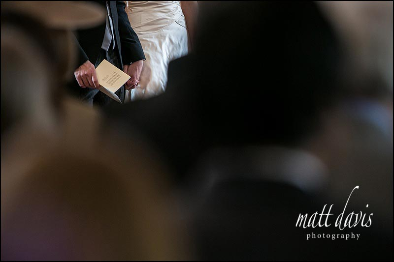 Creative documentary wedding photo of bride and groom holding hands during wedding ceremony