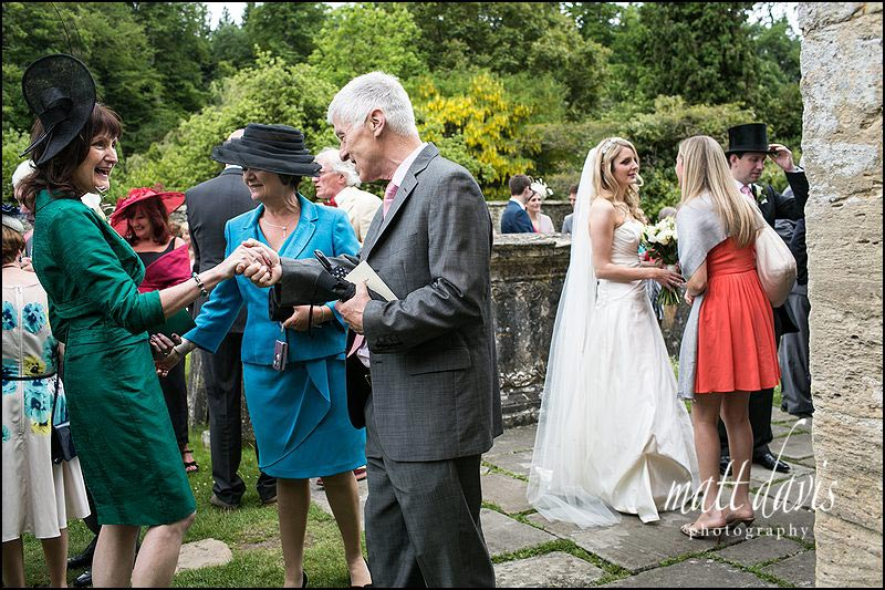 Natural photo of wedding guests outside St Mary's Church, Bibury