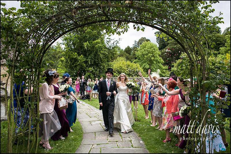 Confetti wedding photo under the arch at Bibury Church Gloucestershire