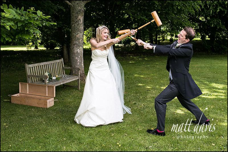 fun Cripps Barn wedding photography of bride and groom playing croquet