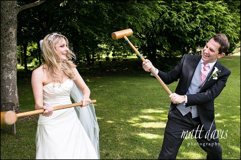 Bride and groom playing croquet at Cripps Barn wedding