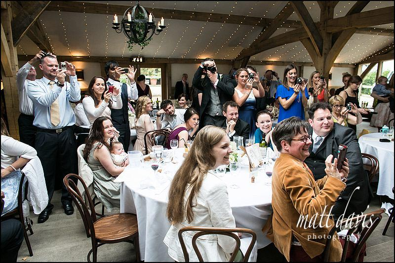 Wedding guests at Cripps barn photographing cutting of the cake