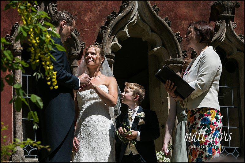 Ring bearer looks on during Rococo Gardens outdoor wedding ceremony