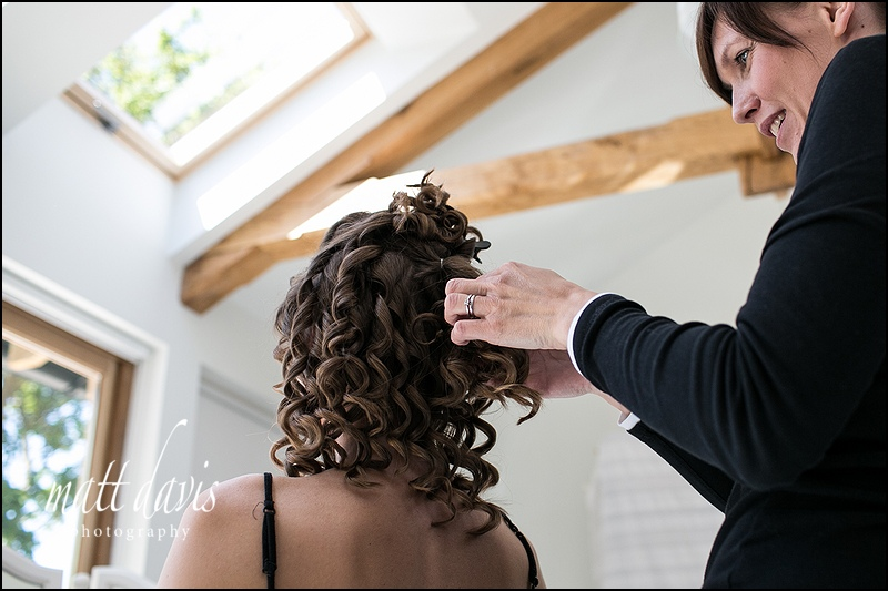 Wedding hair with tight curls tied up at the back