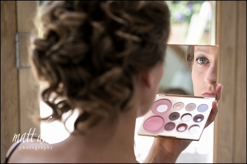 Bride looking in make-up mirror as she has wedding make-up applied