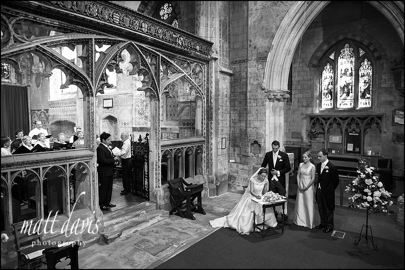 Wedding couple signing the register inside St Mary's church, Berkeley, Gloucestershire