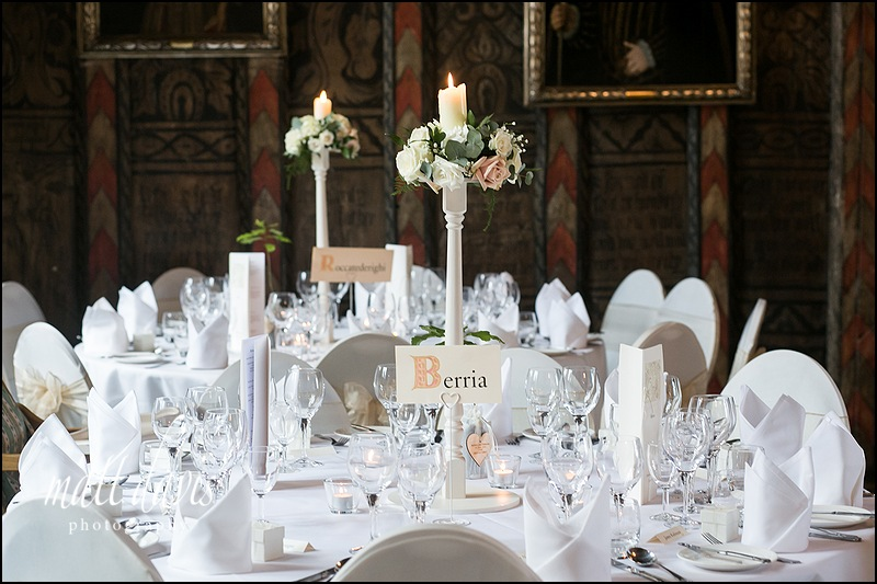 Tall candle arraignment with flowers in the table centers at Berkeley Castle