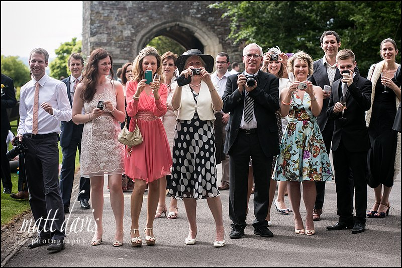 wedding guests on the gun terrace at Berkeley Castle taking photos