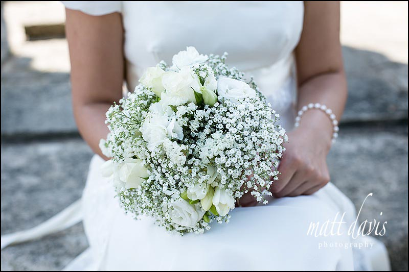 White wedding bouquet with mixed flowers beautifully photographed in brides hands