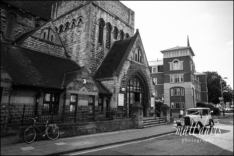 St. Matthew's Church Cheltenham with vintage wedding car parked outside