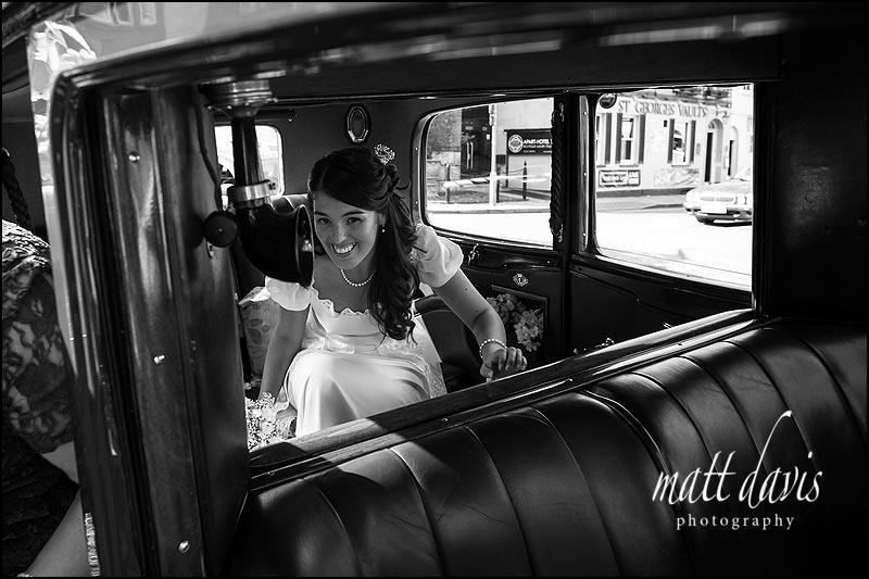 vintage wedding car with bride stepping out in Cheltenham town