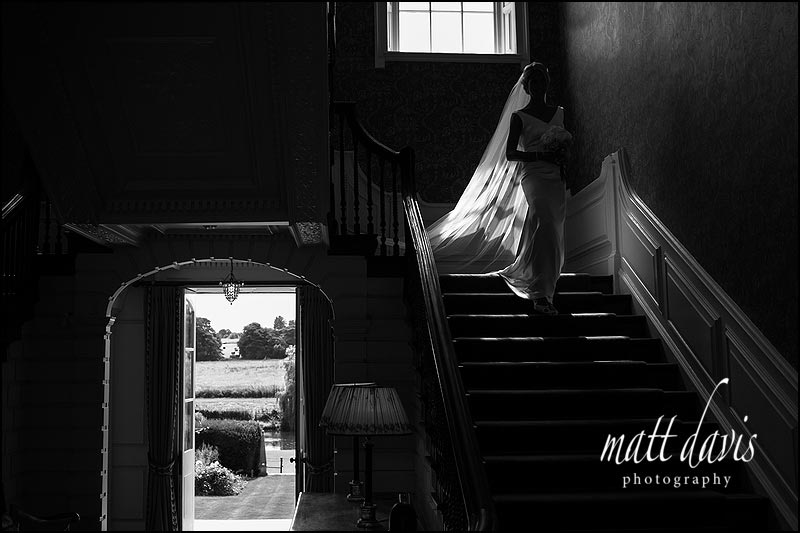 Stunning high contrast black and white wedding photograph of bride on the stairs at Ardington House