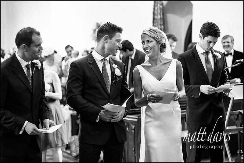 bride smiling at groom during a wedding hymn.