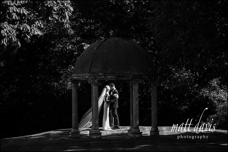 Wedding photo of couple kissing in the gardens of Ardington House