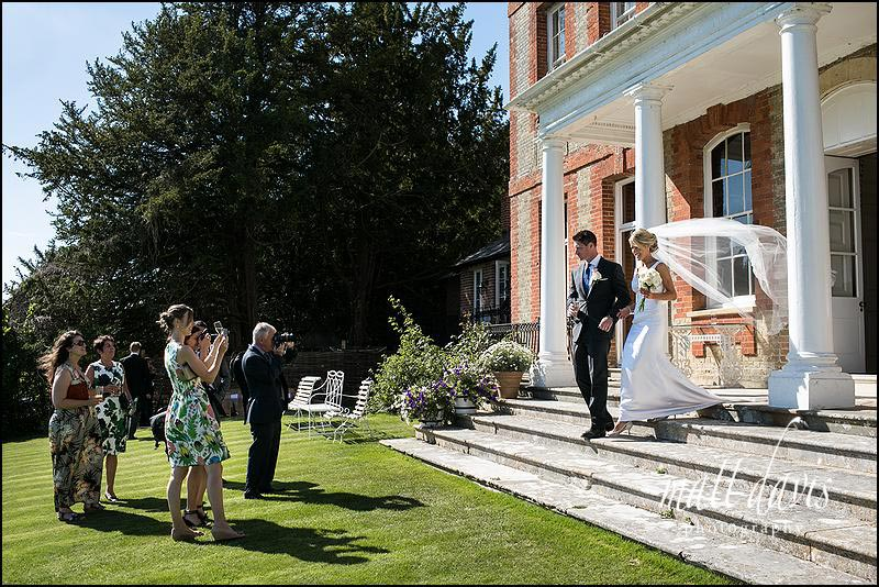 wedding couple step out of Ardington House to be greeted by guests