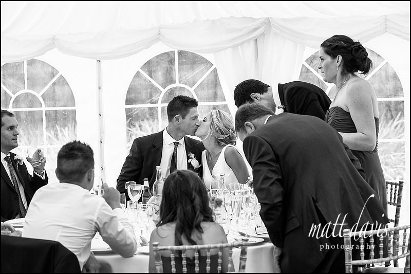 couple kiss during speeches at a wedding at Ardington House