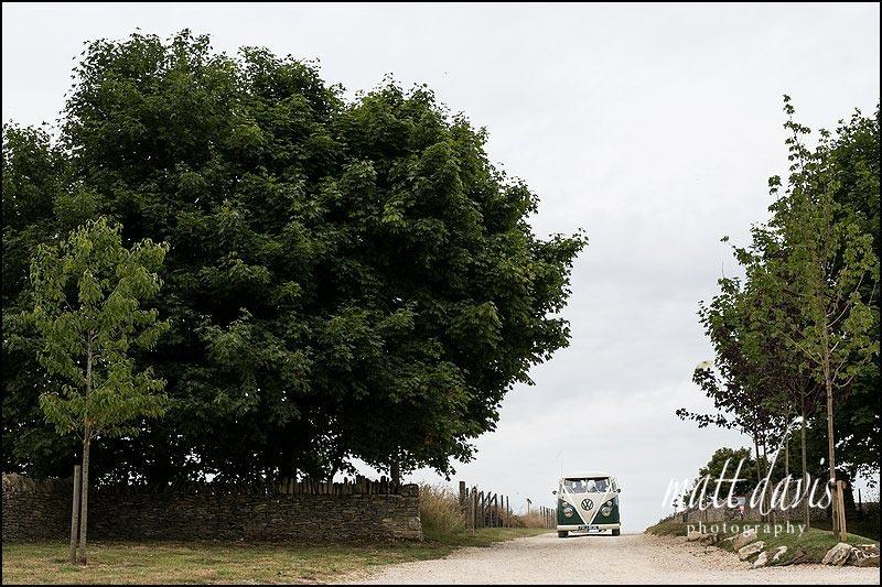 Bride arriving at Cripps Stone Barn in a split screen camper van