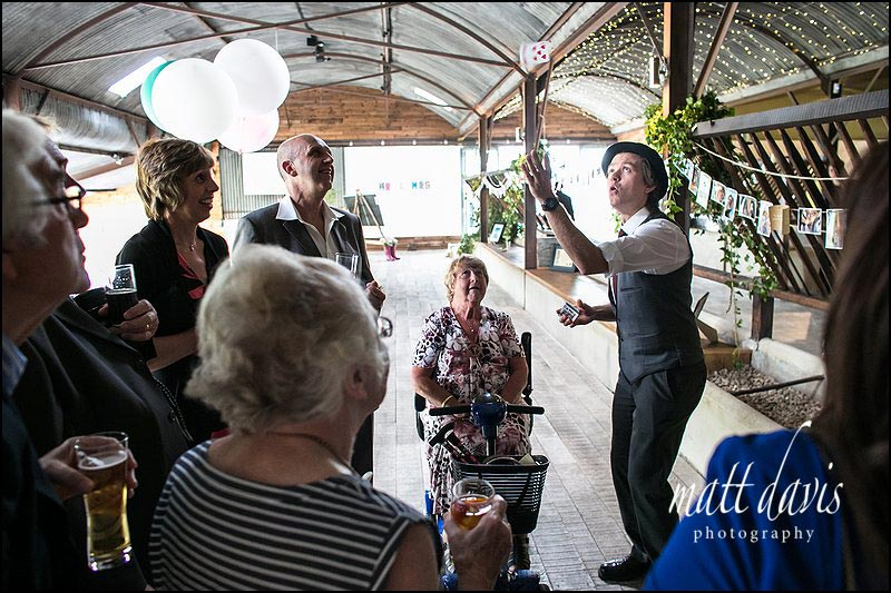 A magician performs tricks at a wedding at Cripps Stone Barn