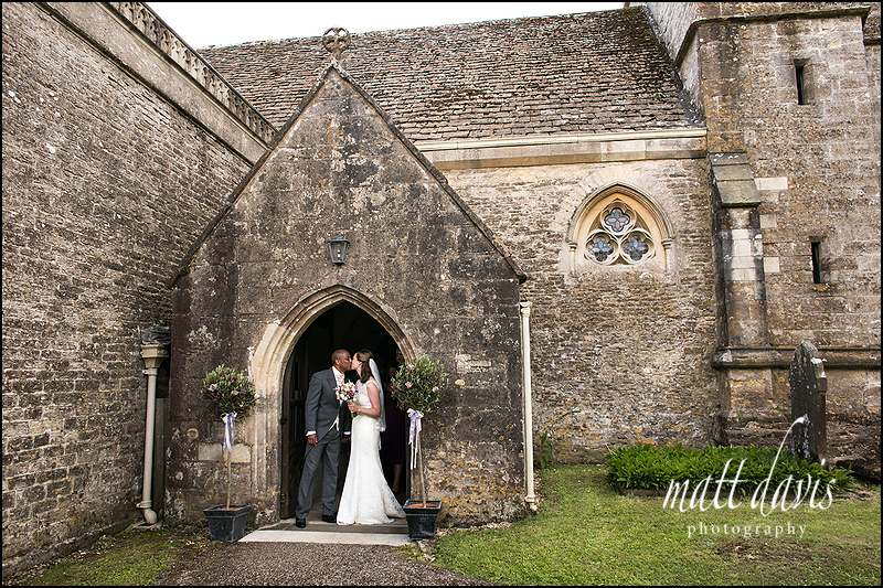 Couple kissing at the doorway of Kingscote Church, Gloucestershire
