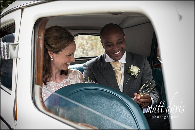 Couple drinking Champagne in a wedding car outside Kingscote Church, Gloucestershire