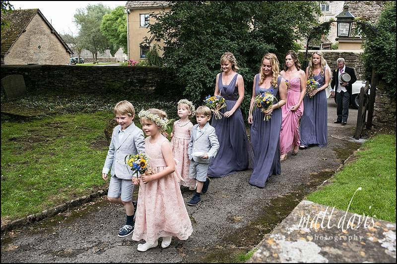 Bridesmaids in Grey/Blue bridesmaids dresses walking into church