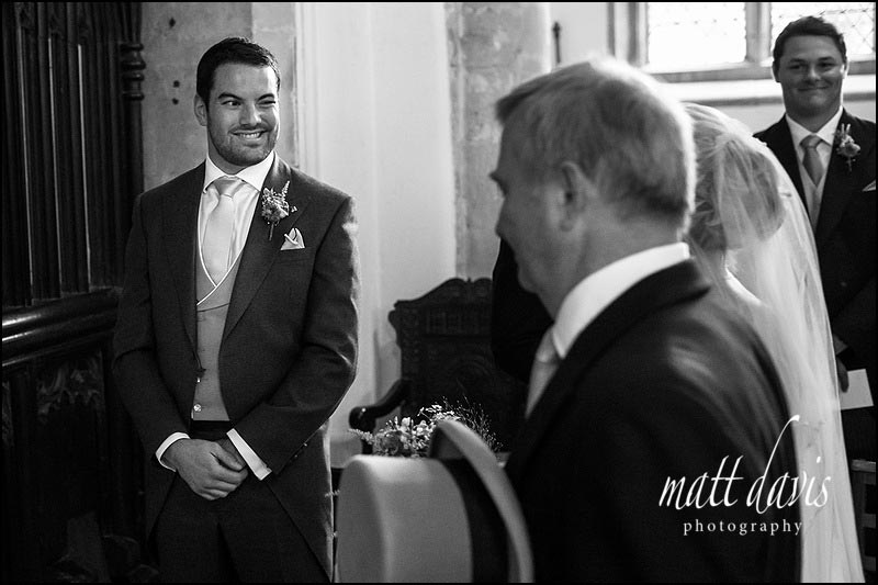 Black and white wedding photo of groom winking at bride as she gets married in the Cotswolds