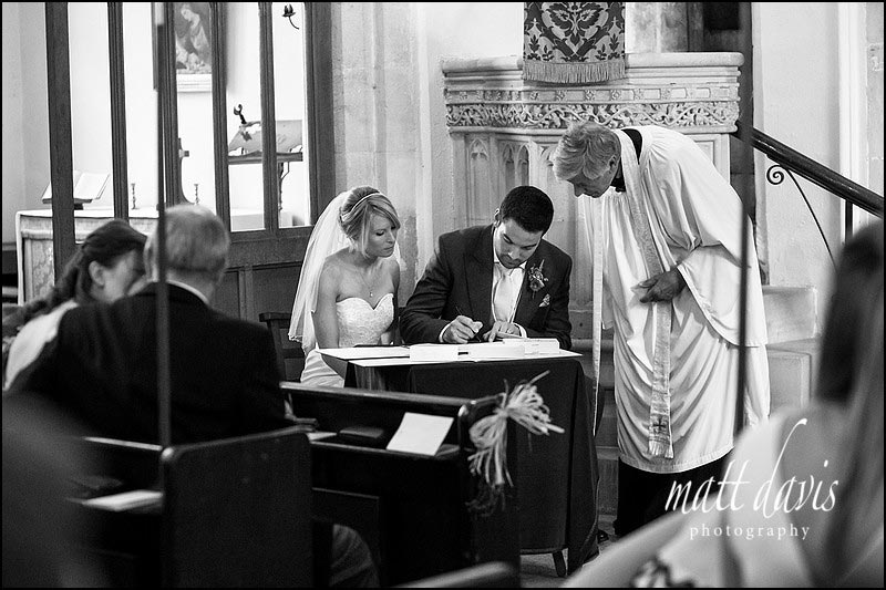 Black and white wedding photos of couple signing the wedding register in Beverston, Gloucestershire