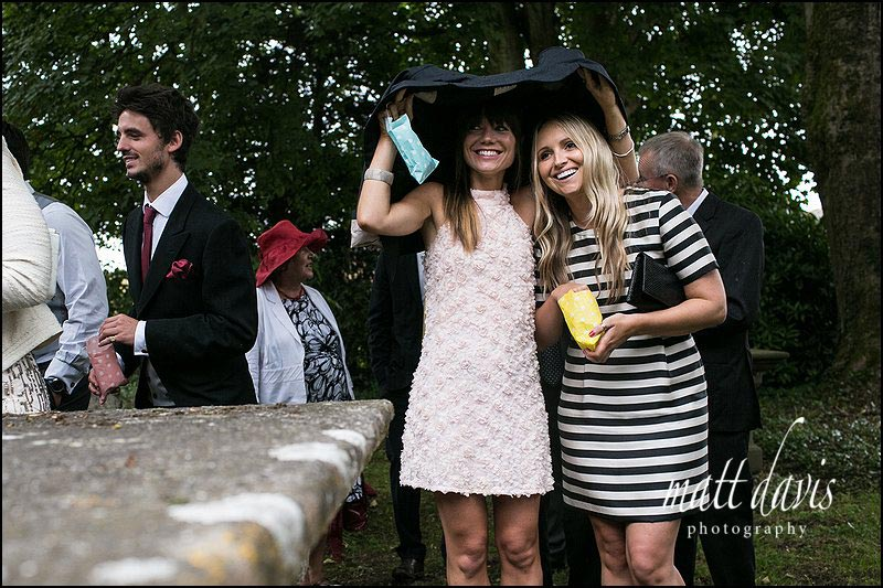 Wedding guests shelter from the rain under a jacket