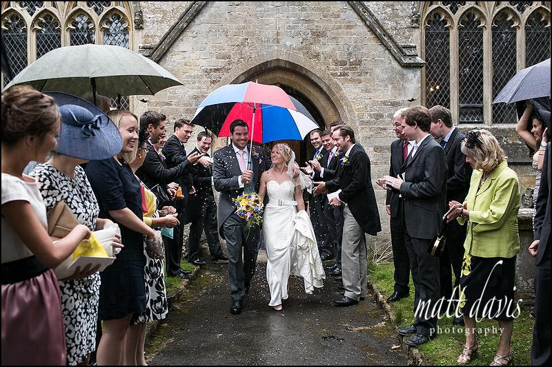 Weddings in the Cotswolds with rain as a couple leave the church and have confetti thrown