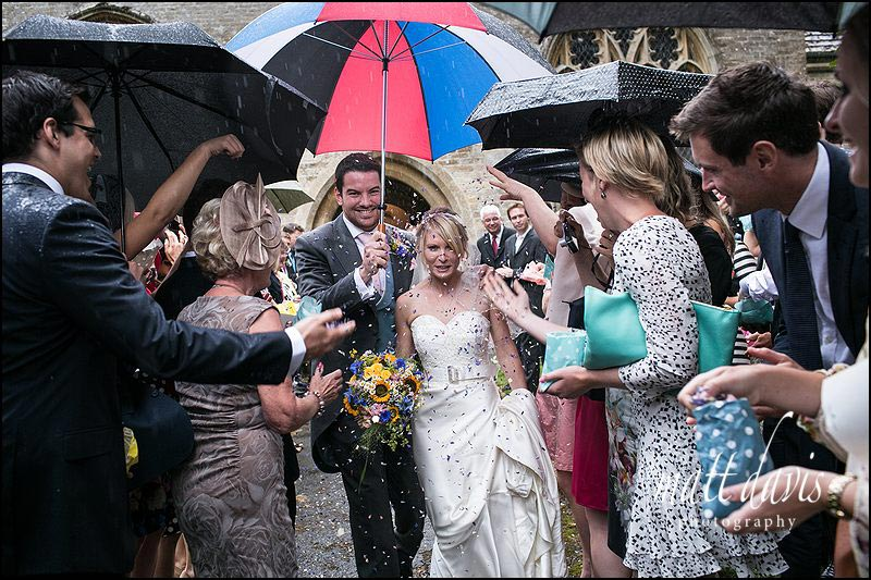 Cotswold weddings with rain as a couple leave the church and have confetti thrown