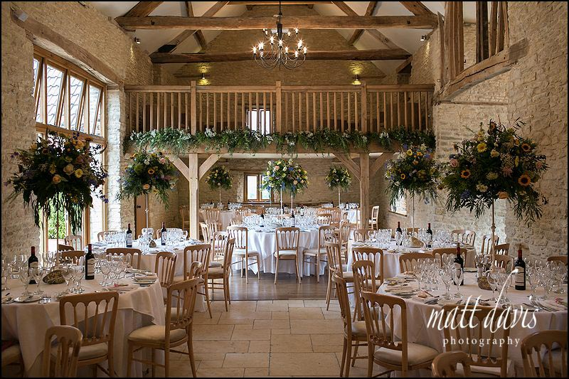 Inside Kingscote Barn with large floral displays