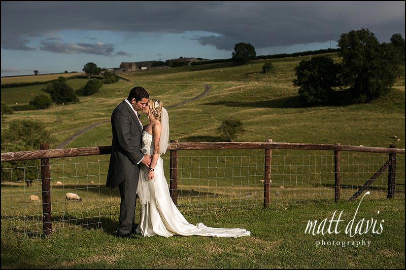 Dramatic wedding photo of couple kissing at Kingscote Barn in the Cotswolds