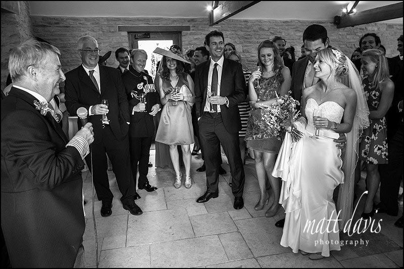 informal wedding speeches inside Kingscote Barn reception room
